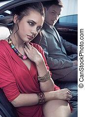 Handsome elegant couple traveling a luxury vehicle
