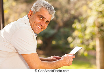 middle aged man holding tablet computer outdoors