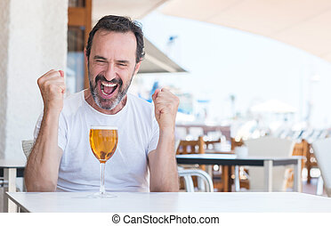 Handsome senior man drinking beer at restaurant screaming proud and celebrating victory and success very excited, cheering emotion