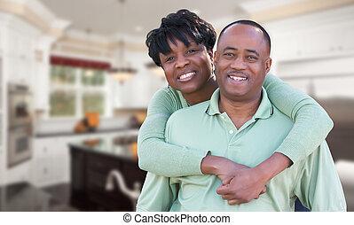 Happy African American Couple Inside Beautiful Custom Kitchen.