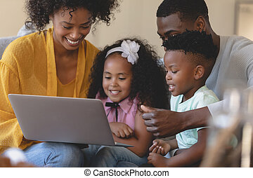Happy African American parents with their cute children using laptop on sofa