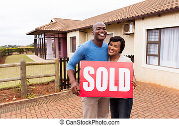 african couple standing outside their house