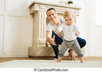 Happy baby trying to stand up while a cheerful father being ready to help