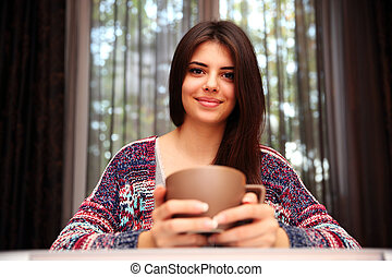 Happy beautiful woman sitting at the table with cup of coffee