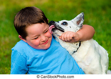 Happy boy being licked by his pet dog