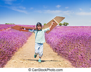 Happy boy waving cardboard wings trying to fly