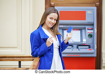 Happy brunette woman withdrawing money from credit card at ATM