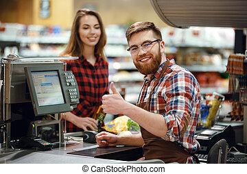 Happy cashier man on workspace in supermarket