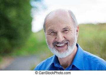 Happy Caucasian retired bearded man, outdoors