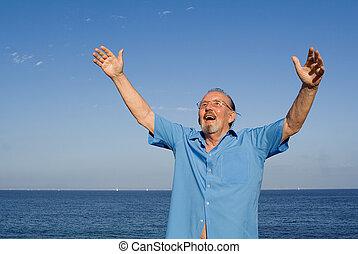 happy christian senior man arms raised in faith and praise