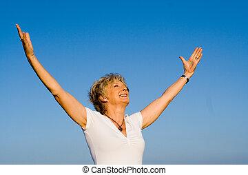happy christian senior woman arms raised in faith and praise