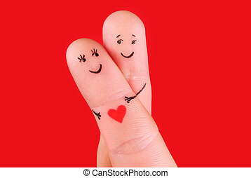 happy couple concept - a man and a woman hug, painted at fingers isolated on red background