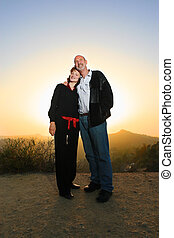 Happy couple embracing outdoors at sunset