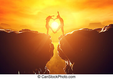 Happy couple in love making heart shape over precipice at sunset.