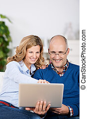 Happy couple sharing a laptop computer