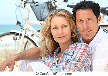Happy couple sitting by the beach with their bikes