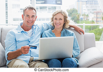Happy couple sitting on their couch using the laptop to buy online smiling at camera at home in the sitting room