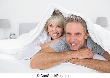 Happy couple smiling under the covers at the camera