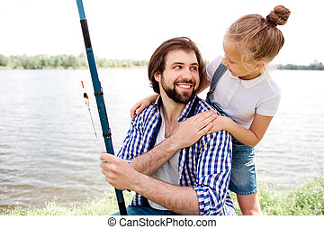 Happy dad is sitting near river shore and looking at his daughter. Also he is holding fish-rod. Girl is standing behind her dad, holding hands on his shulders and smiling. They look happy.