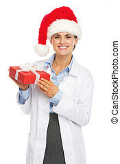 Happy doctor woman in santa hat holding christmas present box