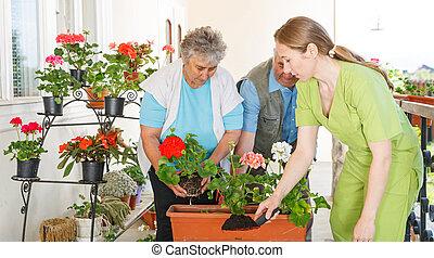 Happy elderly couple planting flower