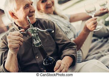 Happy elderly pair going to drink wine