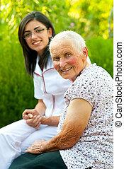 Happy elderly woman outdoors with nurse