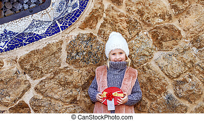 happy elegant child in Barcelona, Spain holding Christmas gift