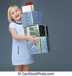happy elegant child on grey holding pile of Christmas giftes