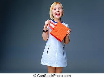 happy elegant child on grey showing red christmas shopping bag