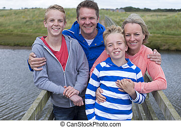 Happy Family of Four standing on a bridge over water. They have their arms around each other and are smiling at the camera.