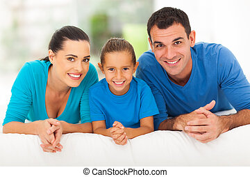happy family of three lying on bed