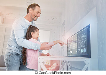 Happy father looking at the screen and helping his daughter to use a computer