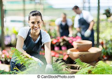 nursery worker trimming plants