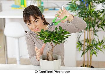 happy female nursery worker trimming plants