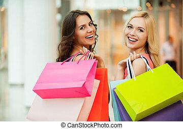 Happy friends shopping. Two beautiful young women enjoying shopping at shopping mall