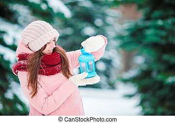 Happy girl holding Christmas candlelight outdoors on beautiful winter snow day