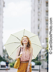 Happy girl walking with umbrella
