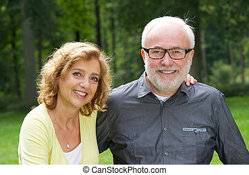 Happy husband and wife smiling outdoors