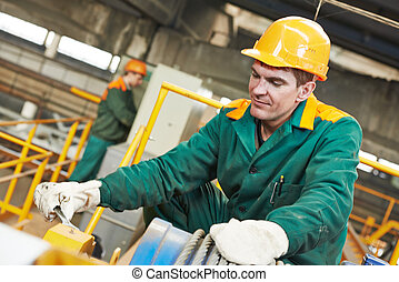 industrial worker with spanner at factory workshop