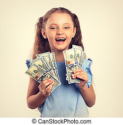 Happy laughing rich kid girl holding money in the hand. Vintage toned portrait