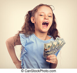Happy laughing rich kid girl holding money the hand. Toned vintage fun portrait