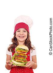 happy little girl cook holding a big hamburger