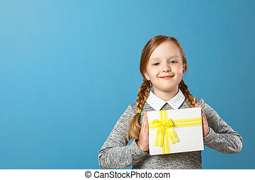 Happy little girl holding box with gift. Portrait of a child on a blue background. Copy space