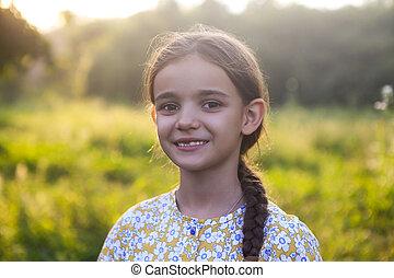 Happy little girl in green field