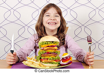 happy little girl with big hamburger on table