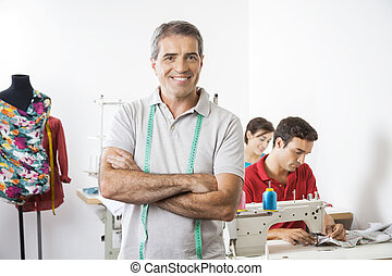 Happy Male Tailor Standing Arms Crossed In Sewing Factory