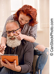 happy man using digital tablet with wife near by