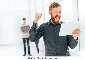 happy man with digital tablet standing in office lobby