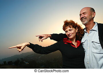 Happy mature couple outdoors at sunset